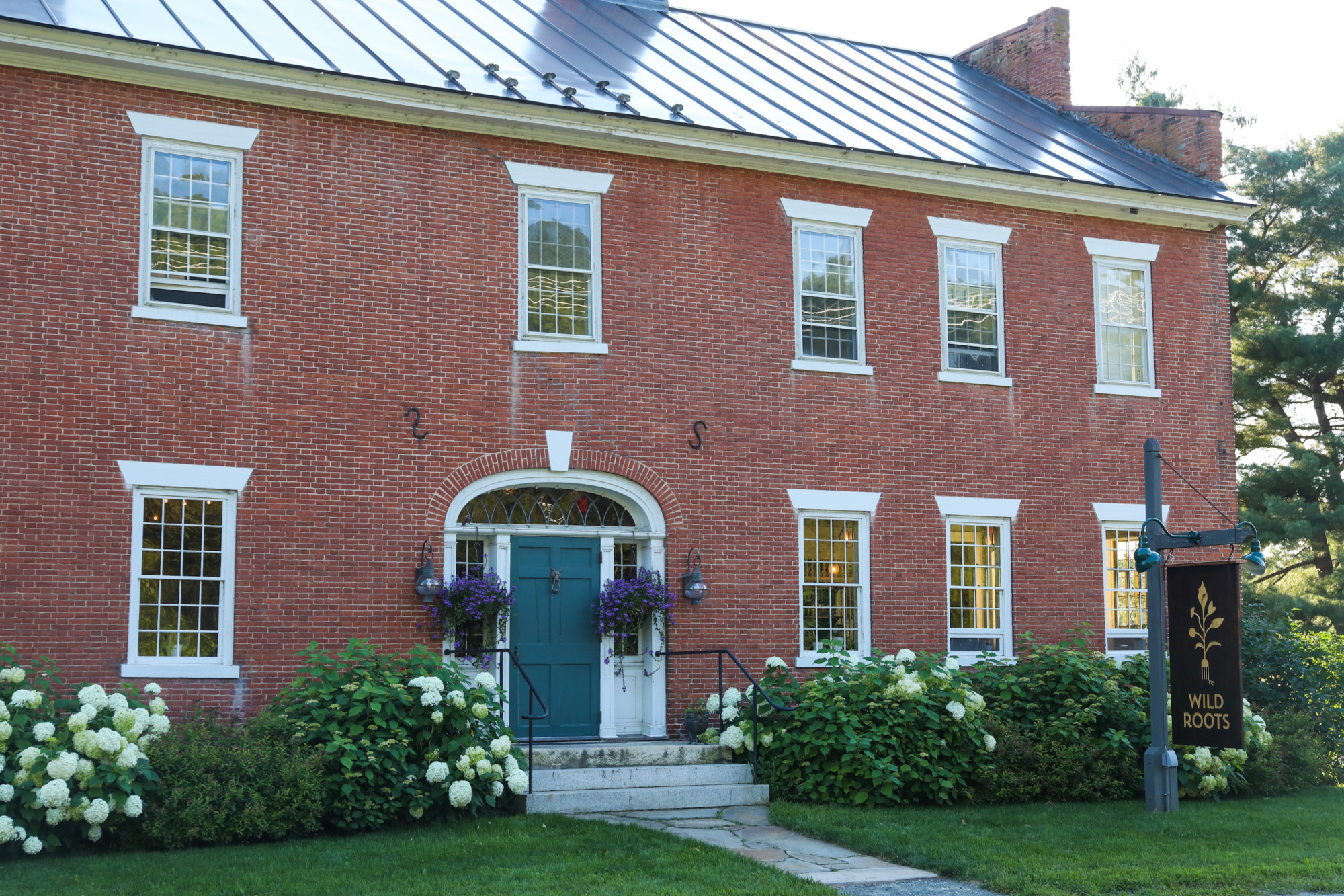 You Walk Into The Front Door Of The Large Brick Colonial, Situated Amongst  A Crowd Of Fluffy White Hydrangeas.
